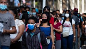 Pessoas usam máscara de proteção em fila da vacinação, em São Paulo
