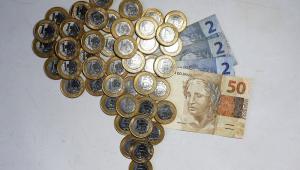 Moedas de R$ 1 formam o mapa do Brasil; do lado direito, há três notas de R$ 2 e uma de R$ 50
