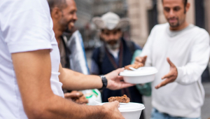 homem recebendo marmita na rua