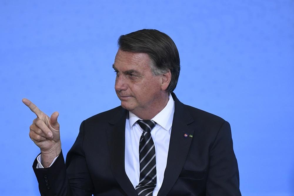 Sob um fundo azul, vestido de terno e gravata, mas sem máscara, Bolsonaro inclina a cabeça para a direita e aponta com o indicador estendido e o polegar levantado