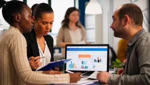 Uma mulher negra, uma morena (que segura uma prancheta azul)e um homem branco de barba discutem trabalho em uma mesa, onde está um notebook que mostra gráficos