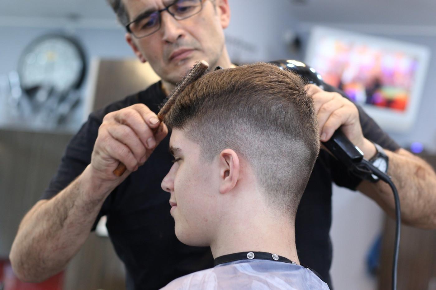 Homem corta cabelo de cliente em um salão de beleza