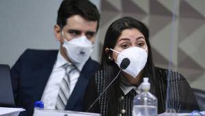Mulher de máscara acompanhada de advogado