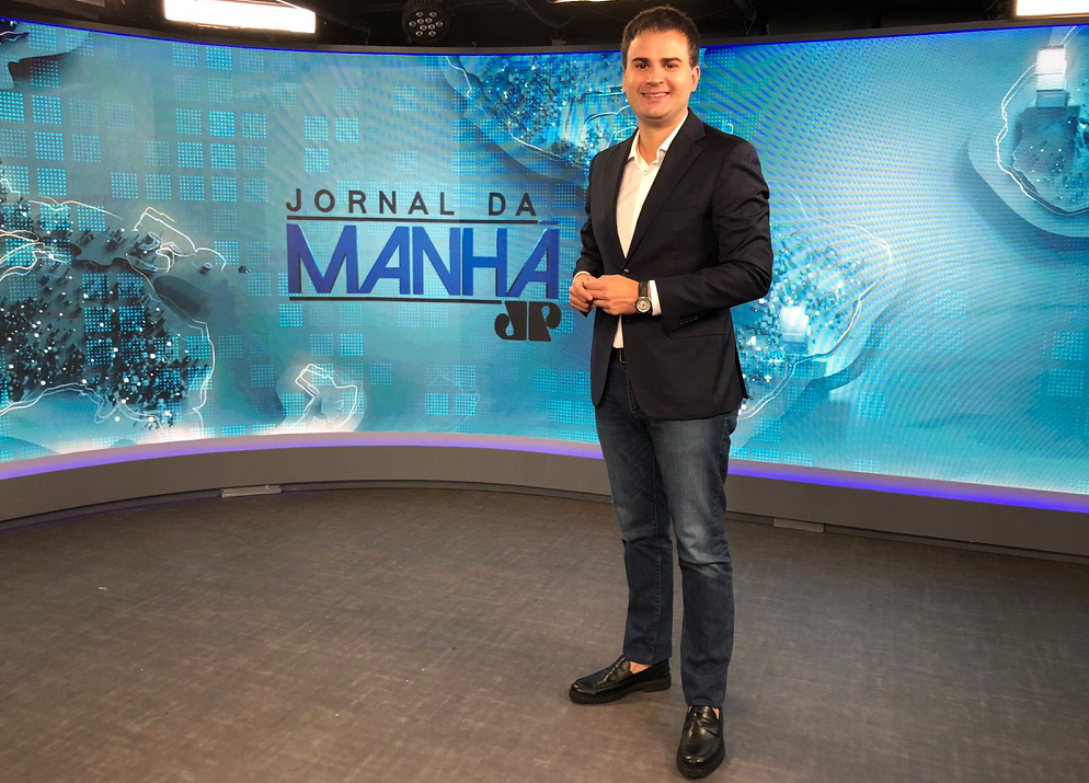 O jornalista Bruno Meyer em pé no estúdio do Jornal da Manhã, com o logo do telejornal ao fundo, vestido com calça jeans, paletó, camisa e sapato, usando um relógio no pulso esquerdo