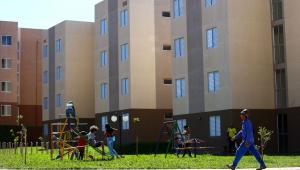 Crianças brincam em um parque dentro de um condomínio de prédios