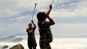 Dois religiosos com blusas camufladas tocando trombeta no Pico do Dedo de Deus, no Rio de Janeiro