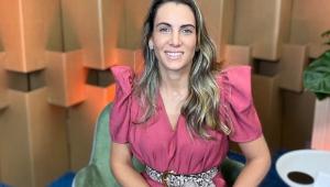 Mulher com cabelo loiro sentada em uma cadeira e sorrindo para a foto. Usa uma espécie de macacão rosa, com um cinto de oncinha. A foto é tirada do peito para cima