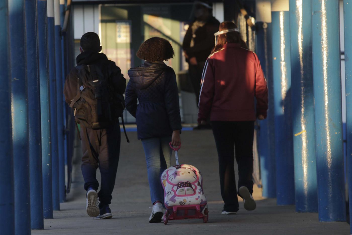 Três alunos com mochilas de costas andando em um corredor da EMEF/EJA Profª Geny Rodriguez, no bairro São Bernardo, em Campinas, interior de São Paulo