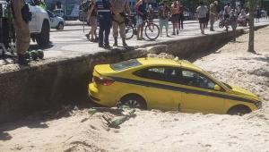 Táxi afundado na areia enquanto pedestres e policiais observam