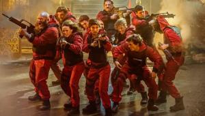 Cena da série La Casa de Papel com os personagens de macacão vermelho e armados