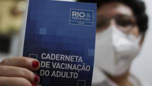 Mulher mostra caderneta de vacinação azul