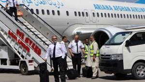 Um comissário de bordo desde de um avião estacionado no aeroporto de Cabul pela escadinha, enquanto outros conversam na pista