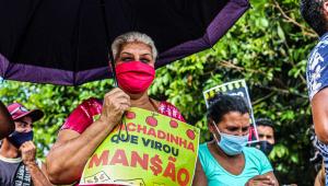Senhora segurando um cartaz escrito 'Rachadinha que virou mansão' em frente à mansão de Flávio Bolsonaro