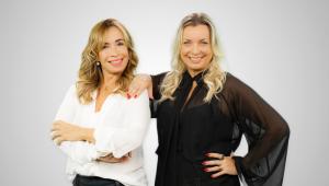 Em foto posada, Fátima Zagari (à esquerda, de branco) e Angélica Greco (á direita, de preto) sorriem, e a última põe a mão no ombro da amiga; as duas são loiras