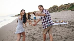 Casal de jovens brancos atraentes de mãos dadas olha para a câmera e faz com as mãos um convite para a festa com amigos que está acontecendo na areia da praia