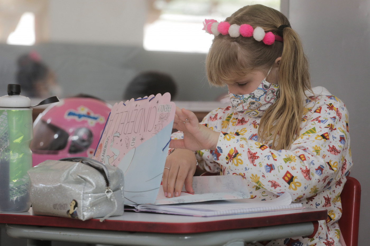 Menina loira mexe em caderno