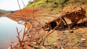 Terra de represa com cores alaranjadas e pouca água. Uma carcaça de carro e galhos aparecem fora d'água