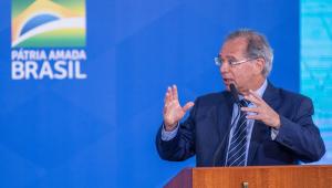 O ministro da Economia, Paulo Guedes, fala à frente de um púlpito com a frase Pátria Amada Brasil atrás dele, na parede azul