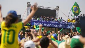 Do alto de um palanque, rodeado de dezenas de aliados, jair Bolsonaro discursa para uma multidão de amarelo na Esplanada dos Ministérios