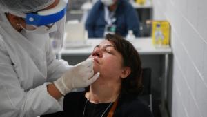 Profissional da saúde realiza teste RT-PCR em mulher