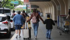 Mulher acompanha crianças e segura mala de viagem