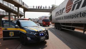 Carro da Polícia Rodoviária Federal estacionado em uma rodovia próxima uma fila de caminhões