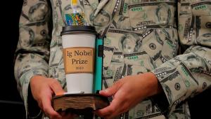 Pessoa segurando uma estatueta que é uma xícara de café com itens, como uma escova de dentes, dentro. Só aparece as mãos e um terno com estampa de dólares