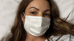 Patrícia Poeta usa máscara e está deitada numa cama de hospital