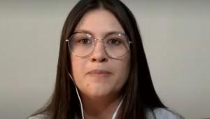 Barbara usa óculos, fones de ouvido e está numa parede branca