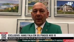 Luciano Hang olhando para a câmera durante participação no programa 'Os Pingos nos Is'. Usa terno verde e gravata amarela