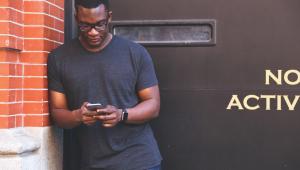 Homem negro em pé olhando para o celular