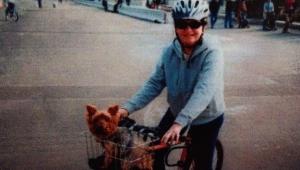 Mulher andando com cachorro em bicicleta