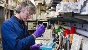 De jaleco e luvas azuis, usando óculos, um cientista de cabelo loiro e enrolado maneja material coletado para possível uso médico