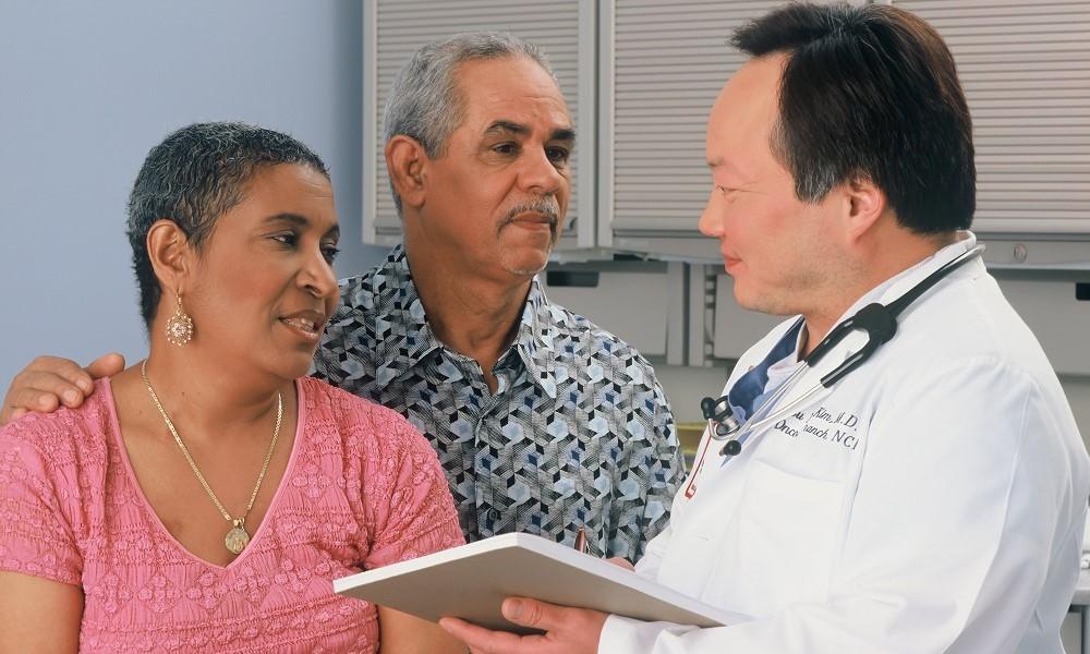 Médico fala com um casal negro