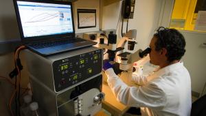 Dentro de um laboratório, médico, vestido com um jaleco branco, olha pela lente de um microscópio para observar resultados de um exame, à sua esquerda, um computado, em altura superior à cabeça do doutor, mostra gráficos