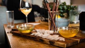 Fatias de peixe cru sobre uma tpábua posta sobre uma mesa, com uma taça de vinho branco ao lado