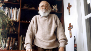 Paulo Freire com suéter claro, em pé, apoiado numa cadeira olhando para a câmera