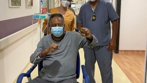 Pelé com as mãos levantadas sentado em uma cadeira no corredor de um hospital