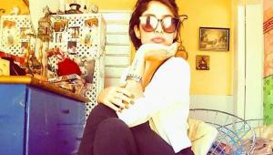Mulher sentada em uma cadeira com a mão segurando o queixo. Usa óculos escuros, camisa branca e calça preta e o cenário é uma espécie de quarto, com penduricalhos, um móvel azul atrás e paredes amarelas