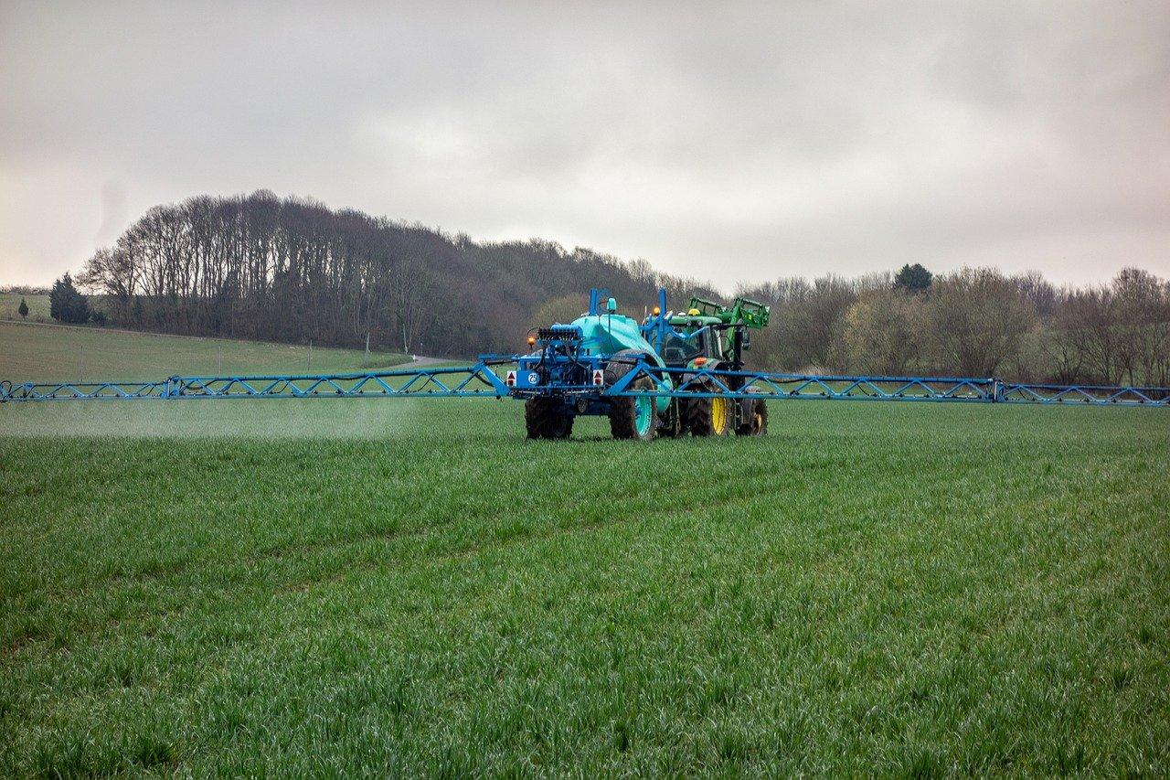 trator jogando fertilizante em plantação