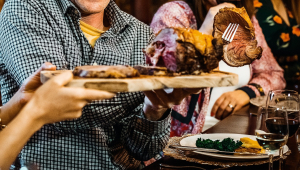 Uma mesa com pessoas se servindo de carne e algumas taças de vinho
