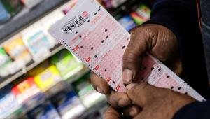 pessoa segurando ticket do powerball, loteria dos eua