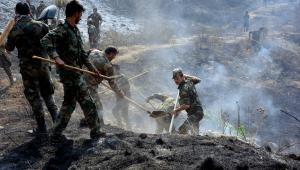 pessoas fazendo rescaldo de incendio na síria