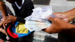 pessoa contando bolivares na rua na Venezuela