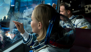 atriz e diretor trajados com roupas espaciais olhando por janela de ônibus
