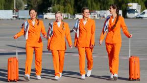 quatro comissárias de bordo vestidas de laranja