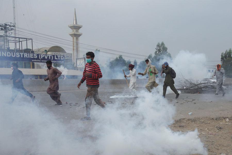 Manifestantes do Tehrik-e-Labaik Pakistan (TLP) fugindo de bombas de gás no Paquistão