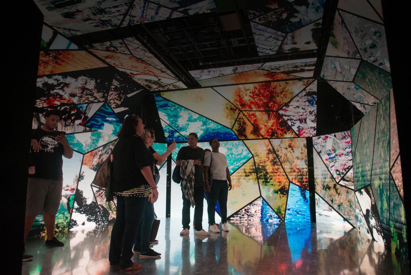 Pessoas admirando um painel na exposição 'O Dia Seguinte'