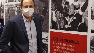 De blazer azul escuro e camisa cinza clara, Rogério Ceni posa em frente a um painel com sua foto nos corredores do Morumbi