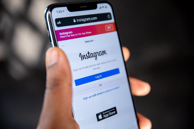 pessoa segurando celular com logo do instagram